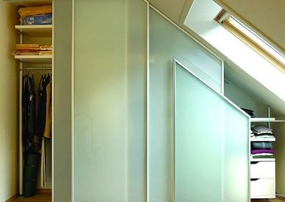 Kleiderschrank mit Gleittüren an einer Dachschräge.